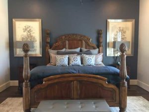 A wooden master bed with blue bedding