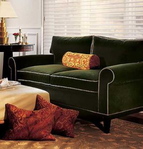 Green Sofa with brown cushions on it