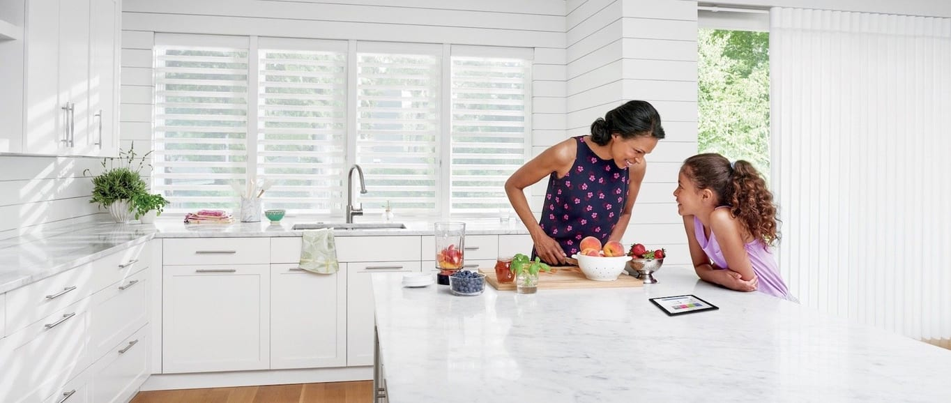 A large kitchen with an island. Shown with Pirouette window shadings, available at Read Design