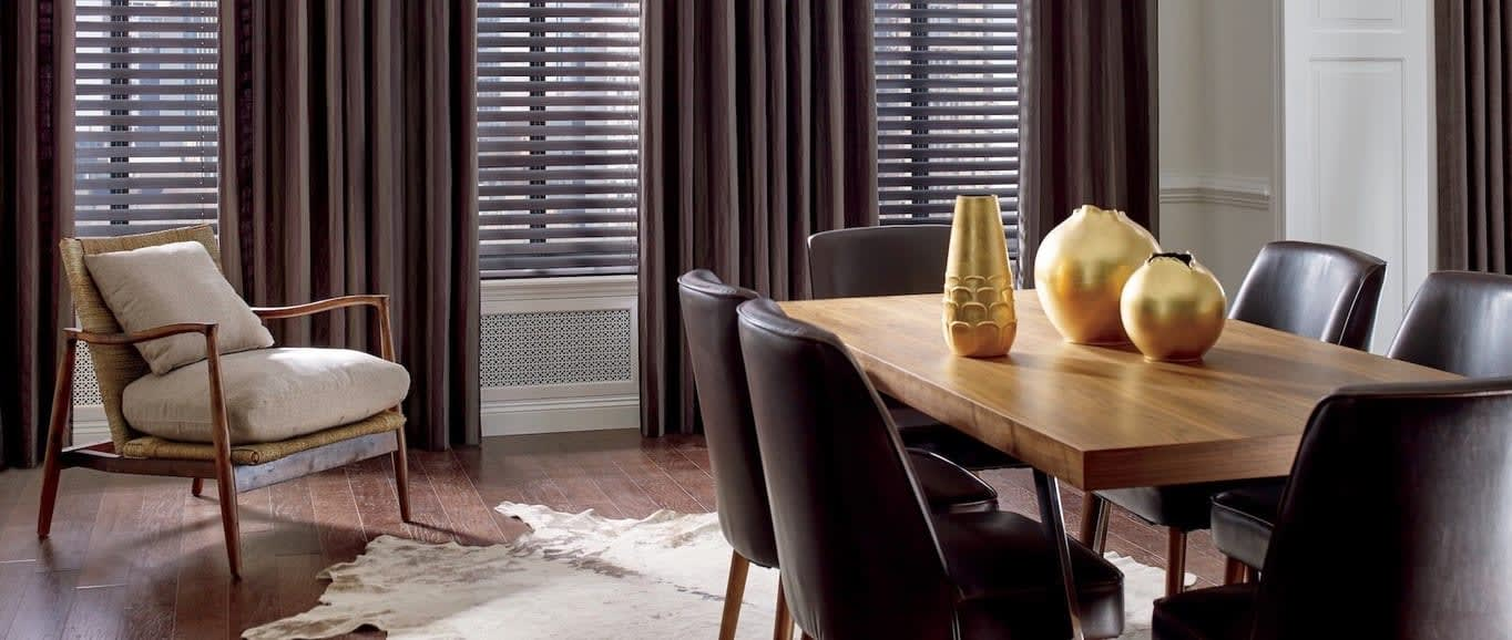 A dining room table with an arrangement of three gold colored vases. Shown with shades from Read Design Window Fashions in Plano.