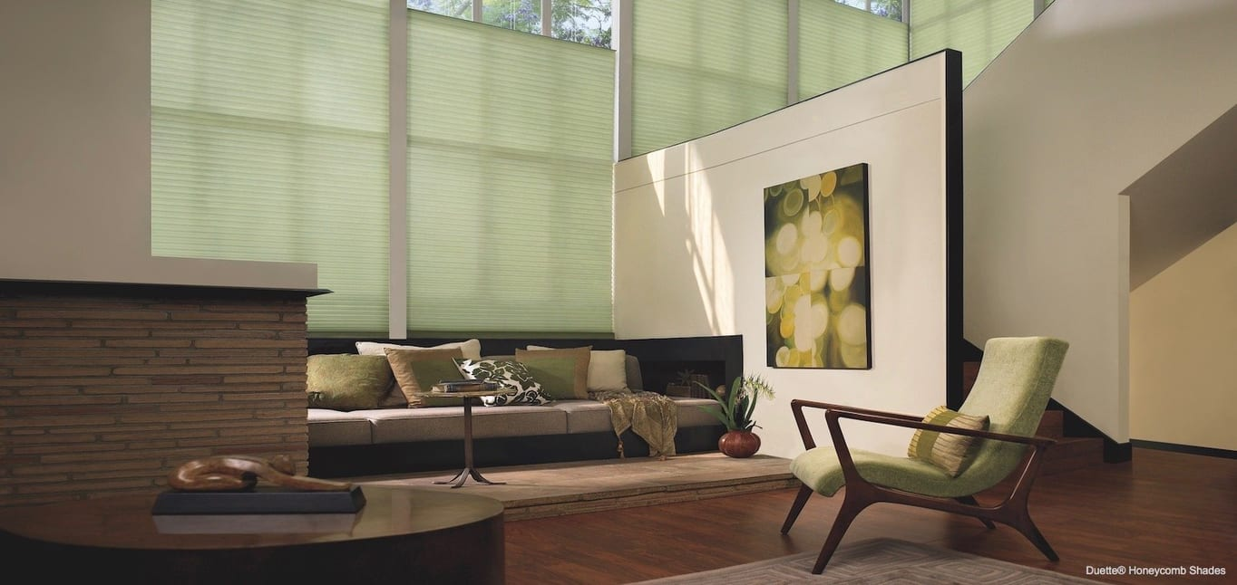 A large painting provides a focal point in this living room. Shown with Duette Honeycomb Shades, available at Read Design