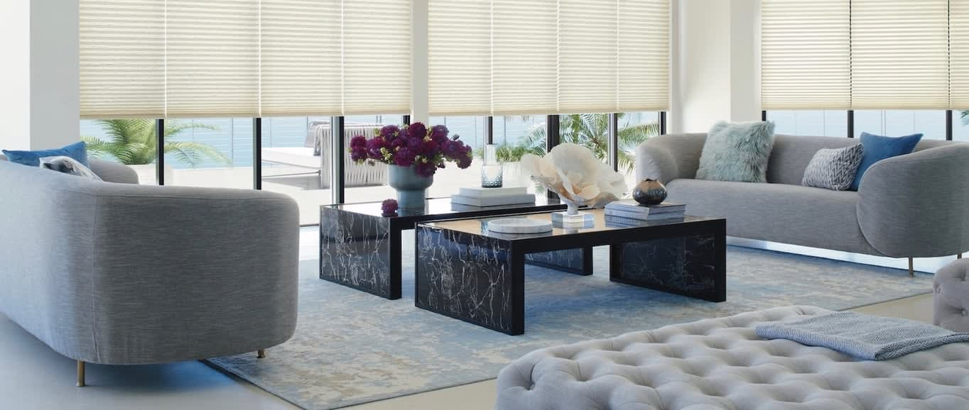 A living room with marble couch tables. Shown with Duette honeycomb shades, available at Read Design
