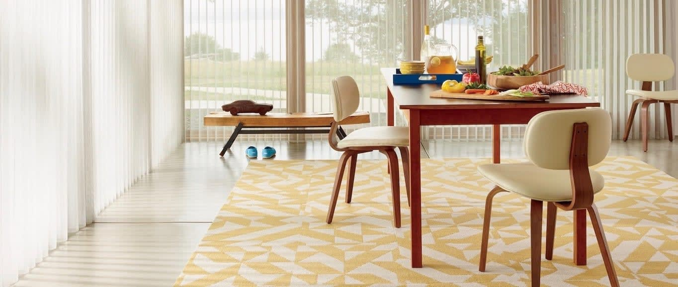 A rug with triangle pattern in a dining room. Shown with Luminette Privacy sheers, available at Read Design