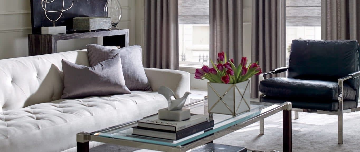 A living room table with fresh tulips. Shown with Hunter Douglas shades from Read Design