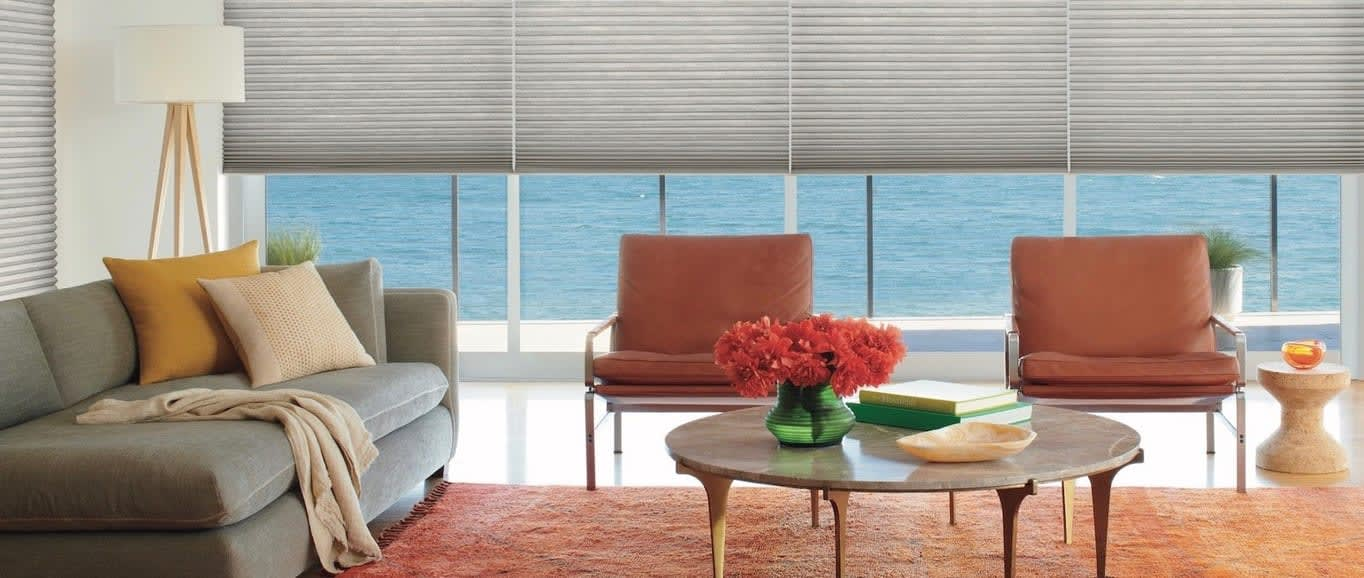 A living room decorated in earth tones. Shown with Duette honeycomb shades, available at Read Design